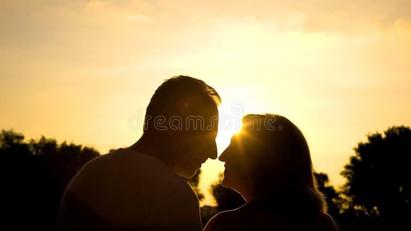 Hombre mayor y mujer que se sonríen, fecha romántica en parque en la puesta del sol, amor fotografía de archivo