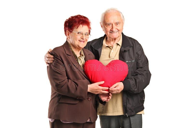 Hombre mayor y mujer que sostienen una almohadilla en forma de corazón fotos de archivo libres de regalías