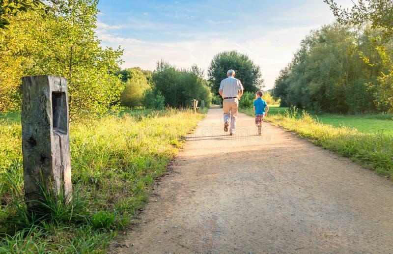Hombre mayor y niño feliz que corren al aire libre fotos de archivo libres de regalías
