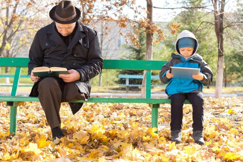 Hombre mayor y pequeño muchacho que comparten un banco de parque fotos de archivo