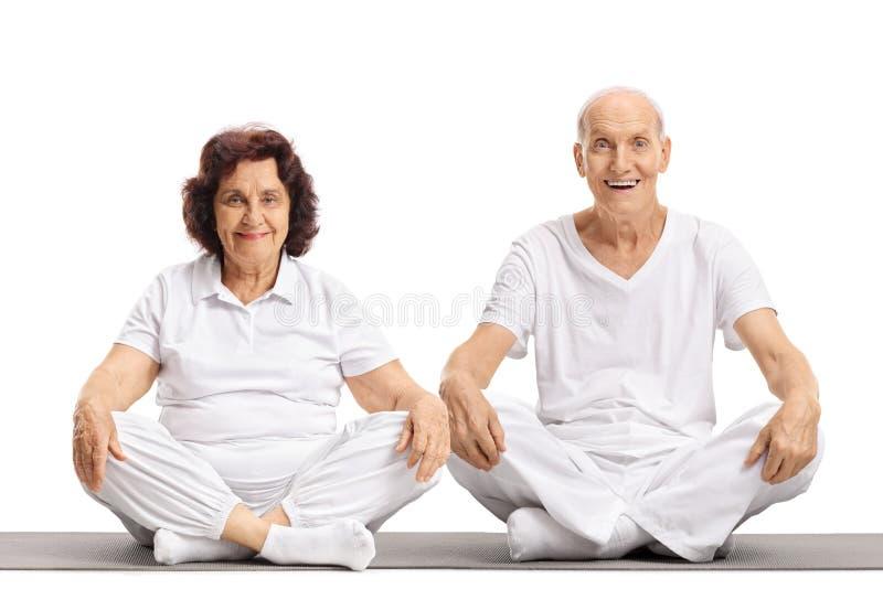 Hombre mayor y una mujer mayor que se sienta en una estera del ejercicio imagenes de archivo