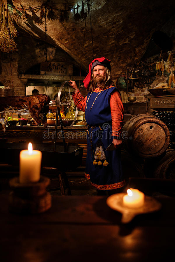 Hombre medieval que hace el cerdo asado en el estante en cocina antigua del castillo foto de archivo libre de regalías