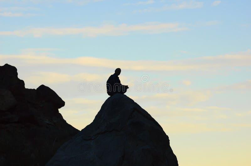 Hombre Meditating que se sienta en tapa en las montañas imagen de archivo