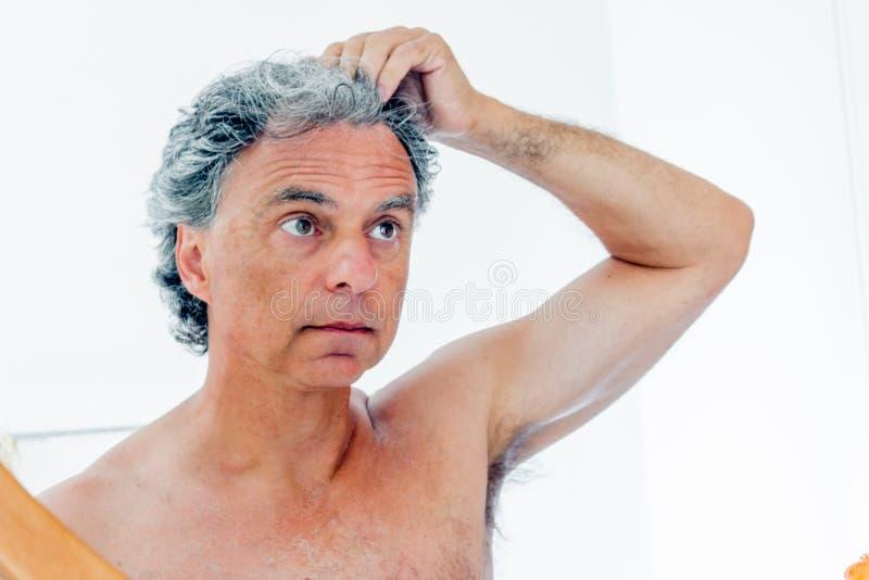 Hombre melenudo descamisado que comprueba su frente foto de archivo libre de regalías