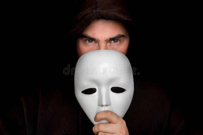 Hombre misterioso en el negro que oculta su cara detrás de la máscara blanca fotografía de archivo