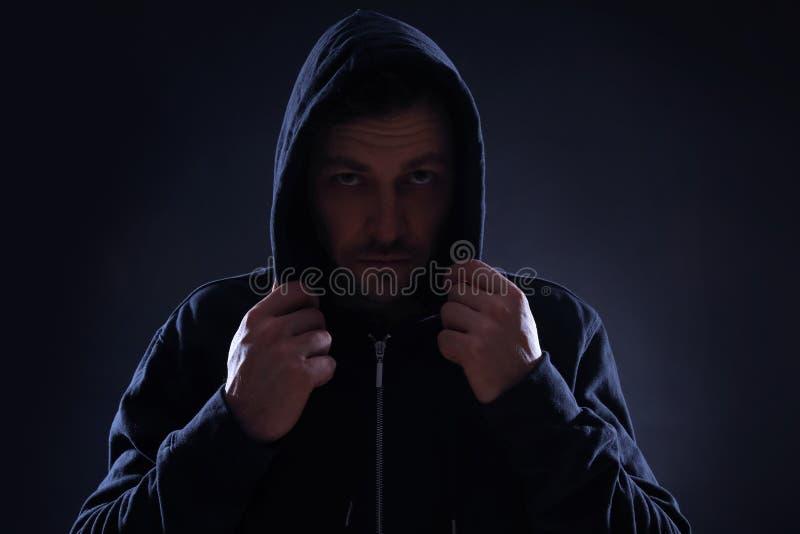 Hombre misterioso en sudadera con capucha en oscuridad Criminal peligroso fotos de archivo libres de regalías