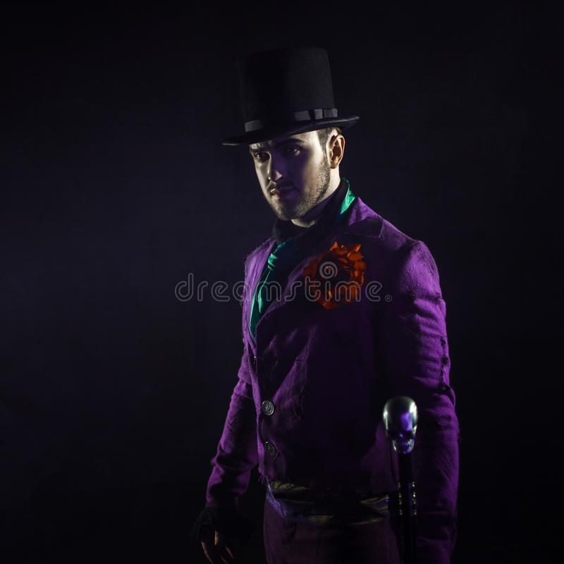 Hombre misterioso en un traje, con un bastón, en un cilindro Fondo oscuro Asustadizo y siniestro Comodín, traje de Halloween imagenes de archivo