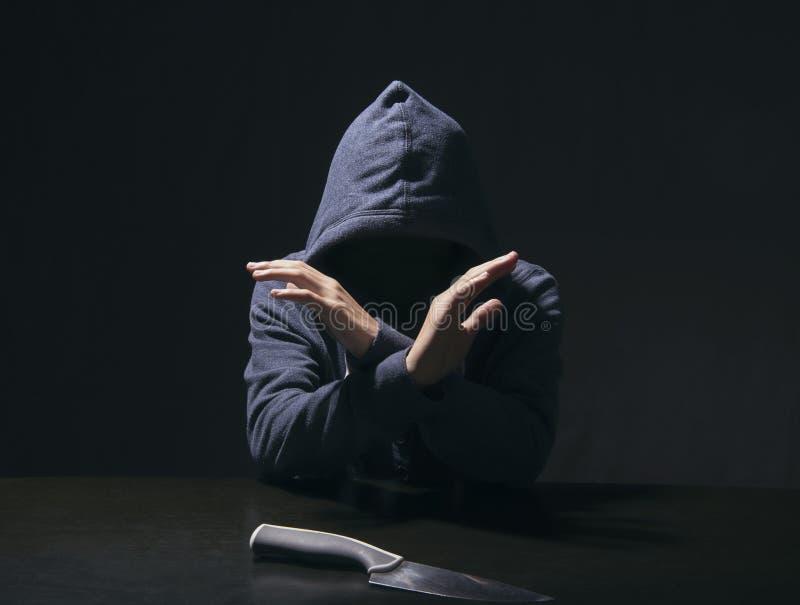 Hombre misterioso encapuchado y cuchillo en sitio de la interrogación confiado fotografía de archivo libre de regalías