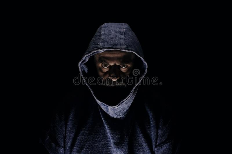Hombre misterioso oscuro con la barba que mira sudadera con capucha azul siniestra, que lleva, en oscuridad total imagenes de archivo