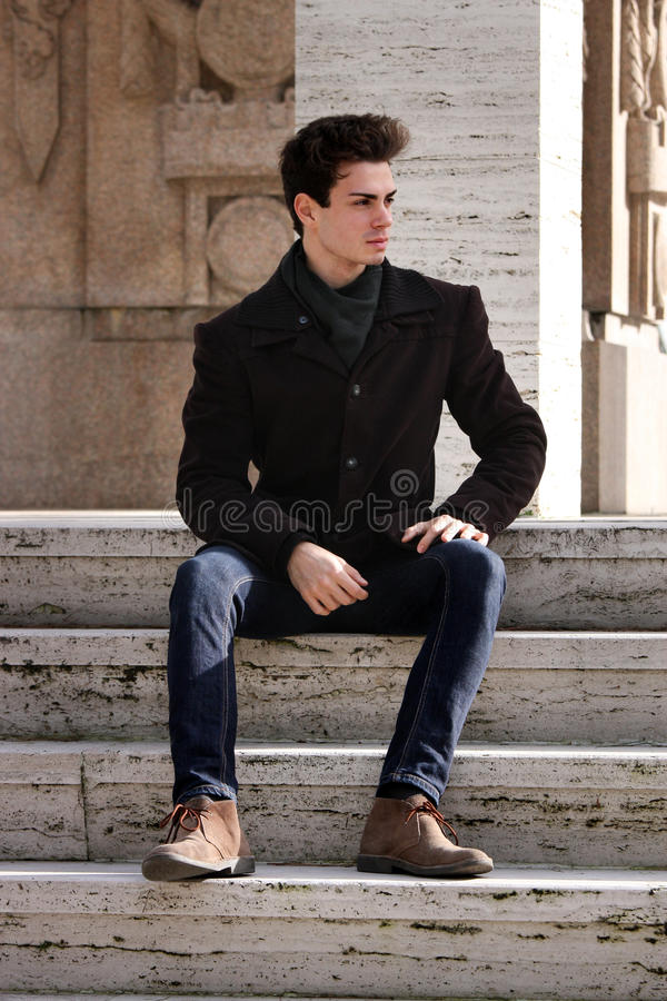 Hombre modelo joven que se sienta en los pasos de mármol foto de archivo libre de regalías