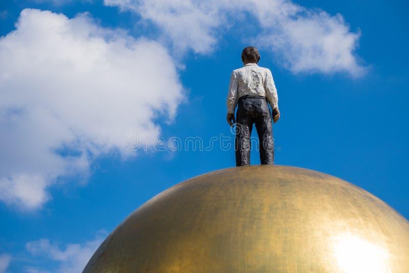 Hombre moderno de la estatua en el oro de la bola fotos de archivo