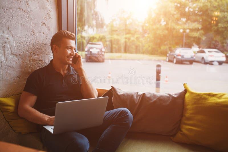 Hombre moderno que trabaja a casa usando el ordenador portátil foto de archivo