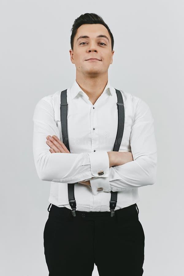 Hombre moreno joven de moda elegante en la camisa blanca, pantalones negros y ligas en el fondo blanco fotos de archivo