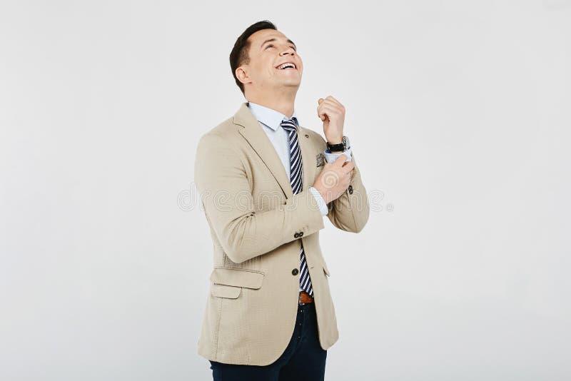 Hombre moreno joven elegante, de moda y hermoso a en la camisa blanca con el lazo rayado, en chaqueta beige y en vaqueros oscuros imagen de archivo