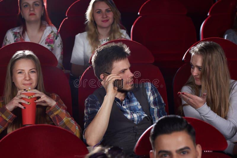 Hombre moreno que habla en el teléfono de la llamada en el pasillo del cine fotos de archivo