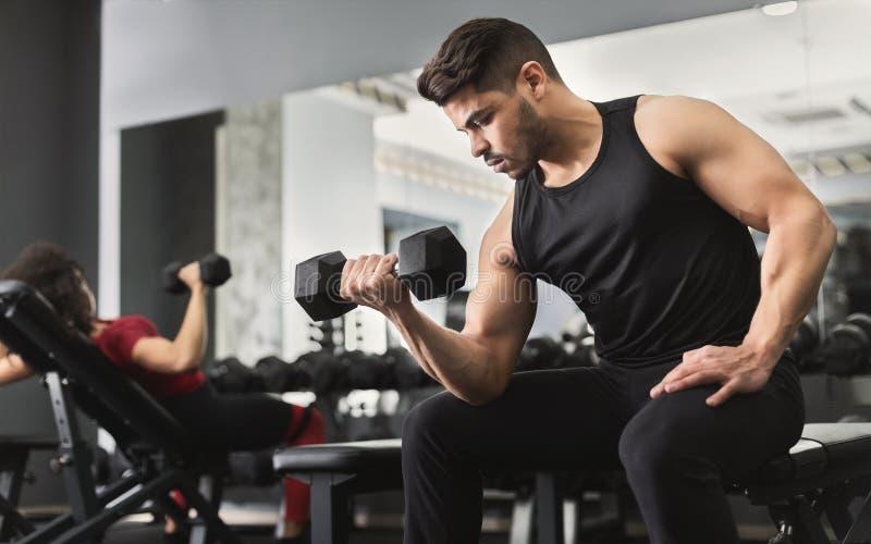 Hombre muscular árabe que hace entrenamientos del bíceps en gimnasio fotografía de archivo libre de regalías