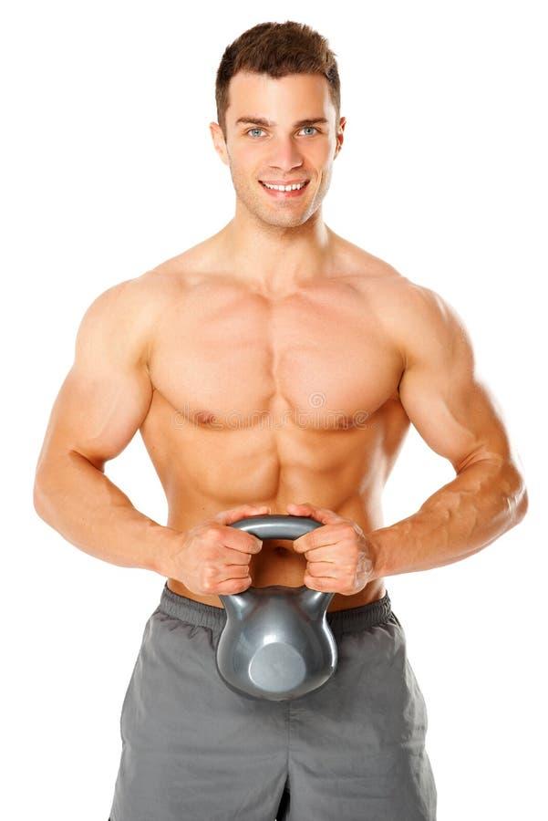 Hombre muscular apto que ejercita con pesa de gimnasia en blanco imagen de archivo