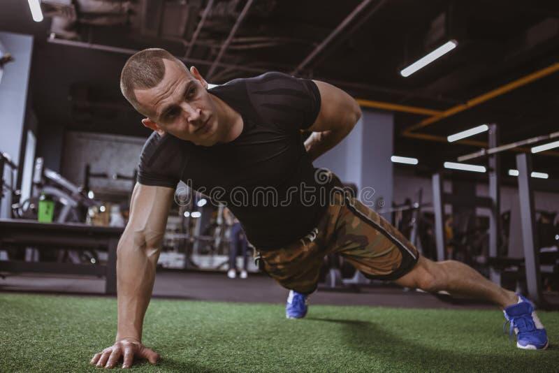Hombre muscular atlético que ejercita en el gimnasio imagen de archivo libre de regalías