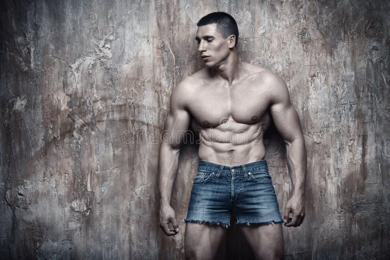 Hombre muscular atractivo hermoso, ABS, en fondo de la pared fotografía de archivo