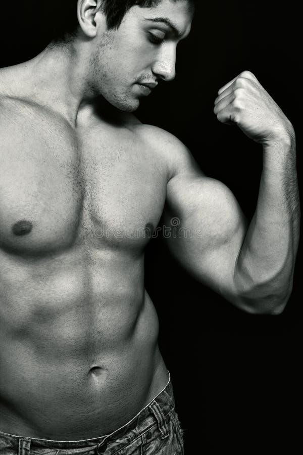 Hombre muscular atractivo que muestra su bíceps foto de archivo libre de regalías