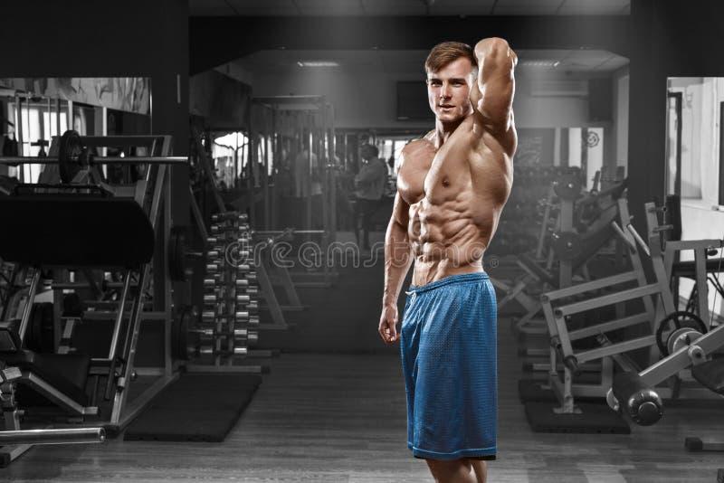Hombre muscular atractivo que presenta en el gimnasio, abdominal formada ABS desnudo masculino fuerte del torso, resolviéndose imagenes de archivo