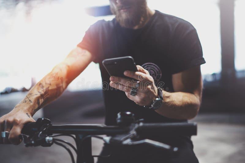 Hombre muscular barbudo tatuado al llevar a cabo las manos del smartphone y usar el app de los mapas antes de montar en vespa elé foto de archivo