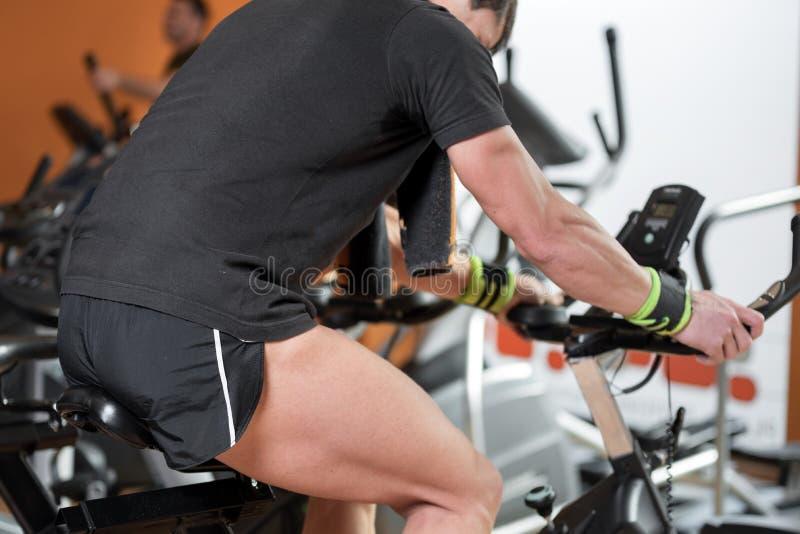 Hombre muscular biking en el gimnasio, ejercitando las piernas que hacen las bicis de ciclo del entrenamiento cardiio, clase de g imagenes de archivo