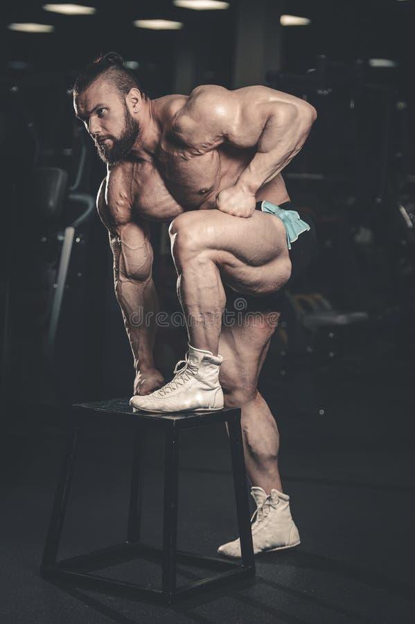 Hombre muscular caucásico del ajuste hermoso que dobla sus músculos en gimnasio imagen de archivo