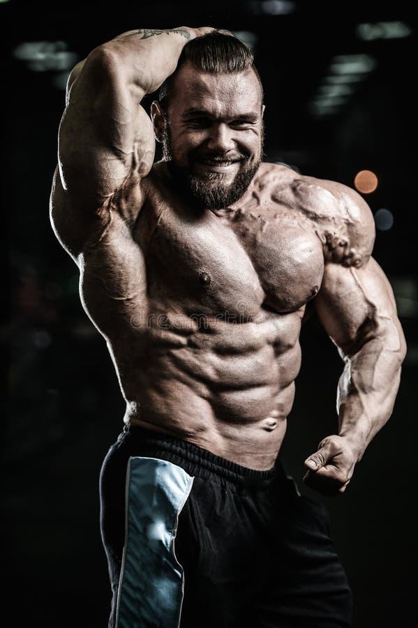 Hombre muscular caucásico del ajuste hermoso que dobla sus músculos en gimnasio fotografía de archivo