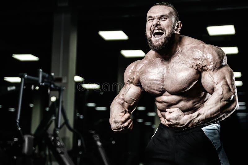 Hombre muscular caucásico del ajuste hermoso que dobla sus músculos en gimnasio fotografía de archivo libre de regalías