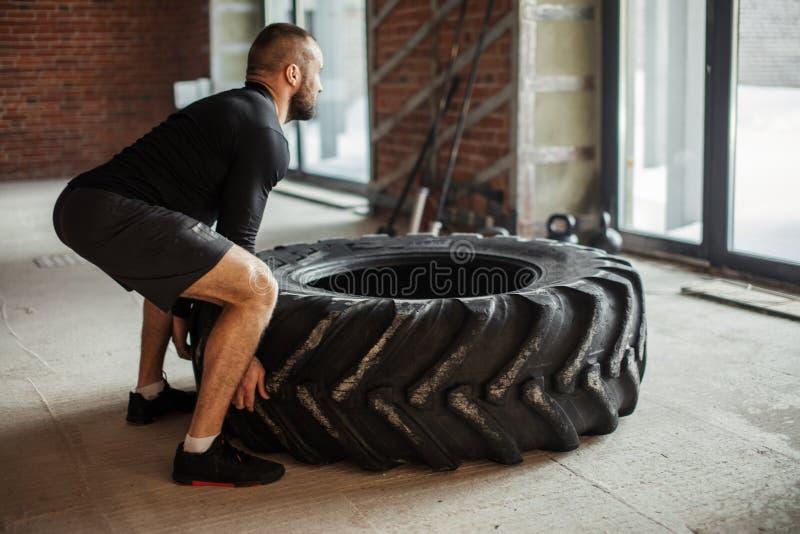 Hombre muscular caucásico joven que mueve de un tirón el neumático pesado en gimnasio imágenes de archivo libres de regalías