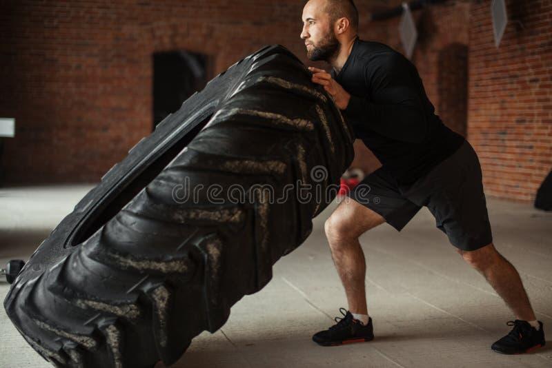 Hombre muscular caucásico joven que mueve de un tirón el neumático pesado en gimnasio fotografía de archivo