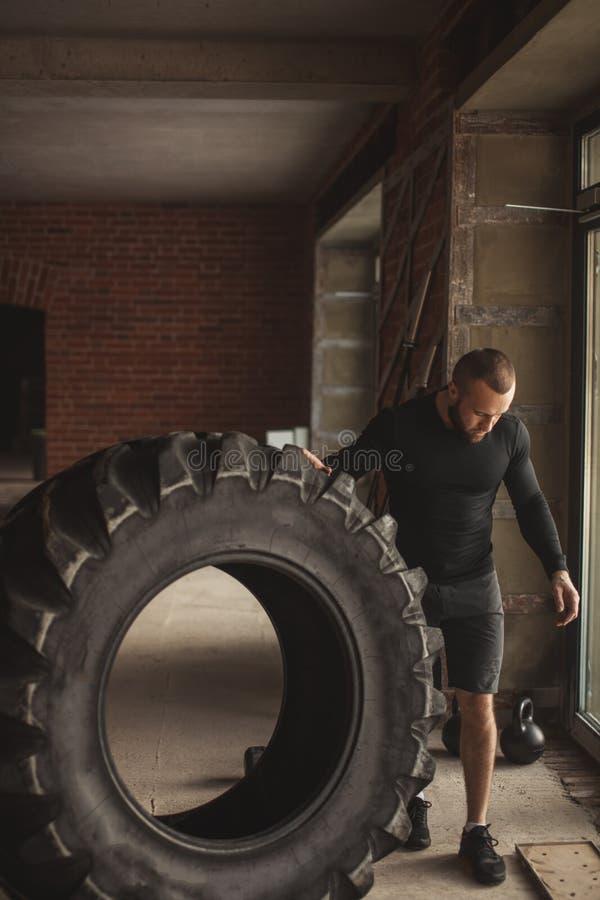 Hombre muscular caucásico joven que mueve de un tirón el neumático pesado en gimnasio imagen de archivo