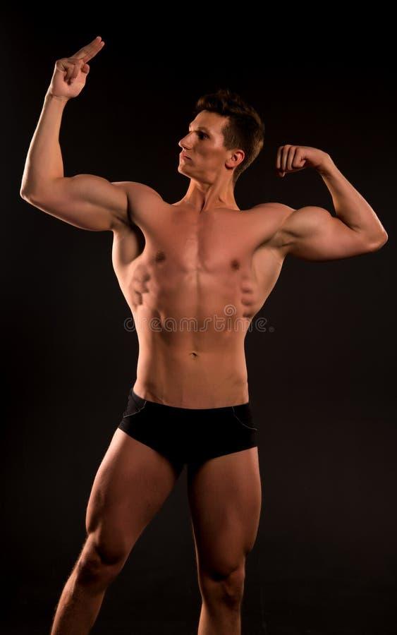 Hombre muscular hombre muscular con ABS punto muscular del culturista del hombre en su músculo bíceps y tríceps del hombre muscul fotografía de archivo