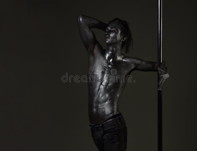 Hombre muscular con el baile de plata del arte de cuerpo en el pilón El hombre atlético hace elementos acrobáticos en el pilón De foto de archivo