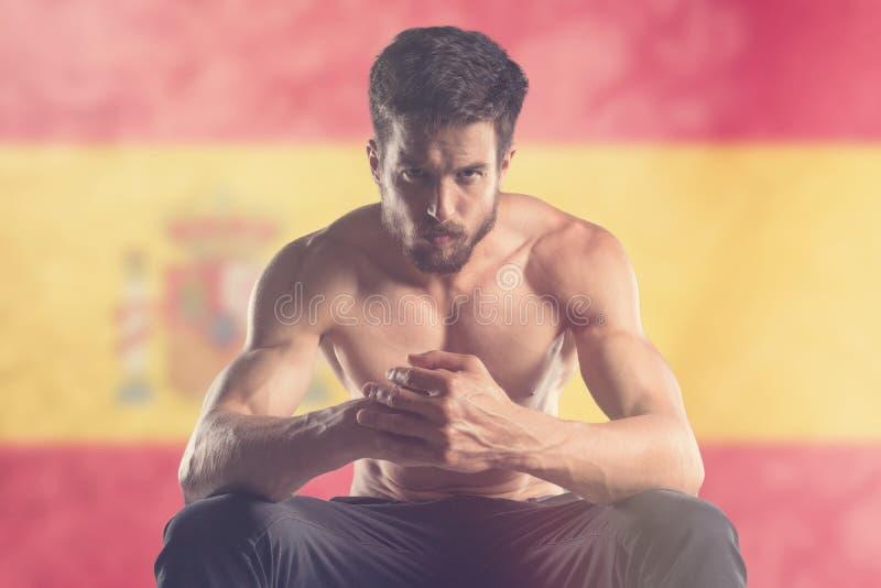 Hombre muscular con la bandera española detrás imagen de archivo libre de regalías