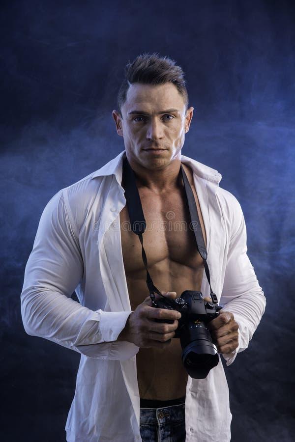 Hombre muscular con la cámara profesional de la foto imágenes de archivo libres de regalías