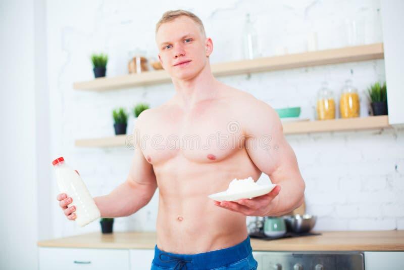 Hombre muscular con un torso desnudo en la cocina con la leche y el requesón, el concepto de una dieta sana Manera atlética imagen de archivo libre de regalías