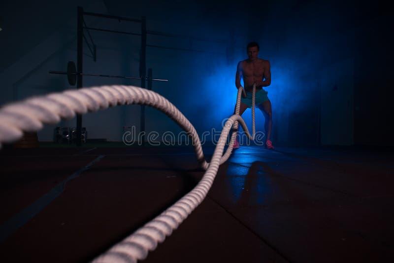 Hombre muscular de la aptitud que ejercita con las cuerdas de la batalla imágenes de archivo libres de regalías