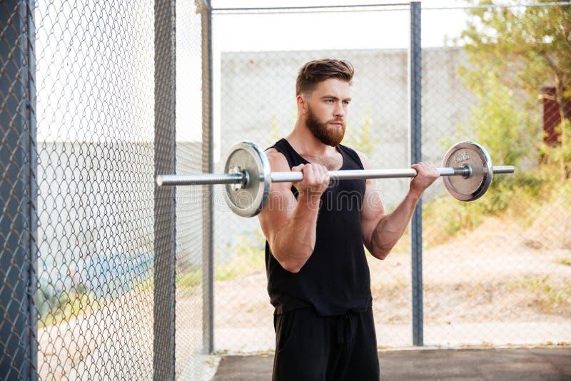 Hombre muscular de la aptitud que hace ejercicio pesado usando barbell al aire libre imagenes de archivo