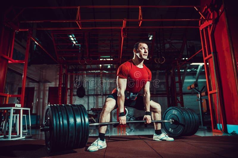 Hombre muscular de la aptitud que hace el deadlift un barbell en centro de aptitud moderno Entrenamiento funcional fotos de archivo
