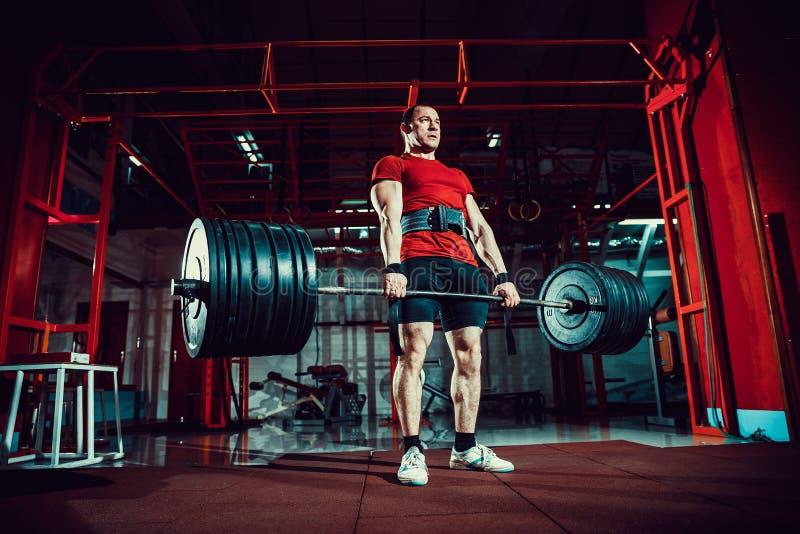 Hombre muscular de la aptitud que hace el deadlift un barbell en centro de aptitud moderno Entrenamiento funcional imagen de archivo