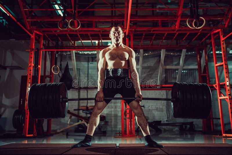 Hombre muscular de la aptitud que hace el deadlift un barbell en centro de aptitud moderno Entrenamiento funcional foto de archivo libre de regalías
