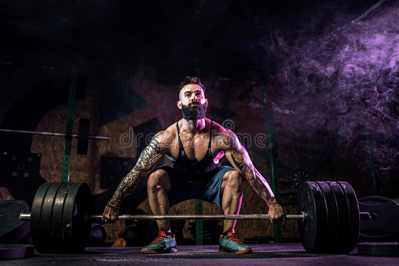 Hombre muscular de la aptitud que hace el deadlift de un barbell en centro de aptitud moderno Entrenamiento funcional fotografía de archivo libre de regalías