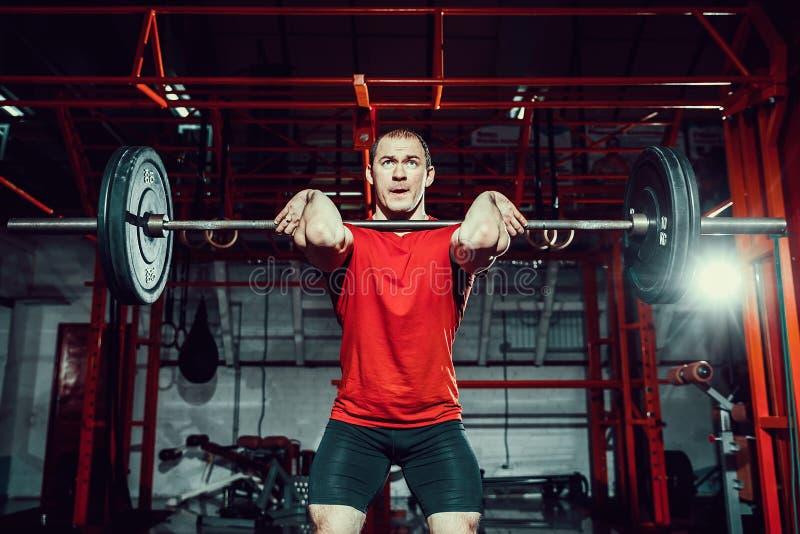 Hombre muscular de la aptitud que hace el deadlift un barbell sobre su cabeza en centro de aptitud moderno Entrenamiento funciona fotos de archivo libres de regalías