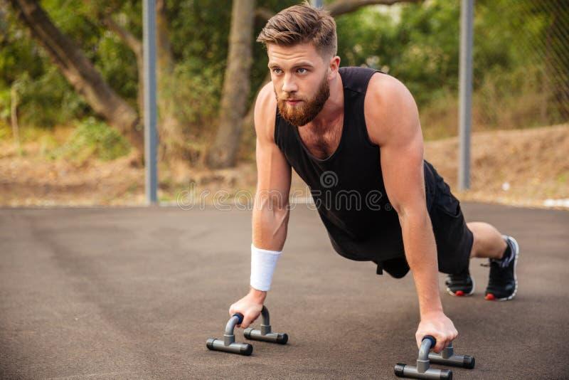 Hombre muscular de la aptitud que hace pectorales y que usa el equipo de deportes imágenes de archivo libres de regalías