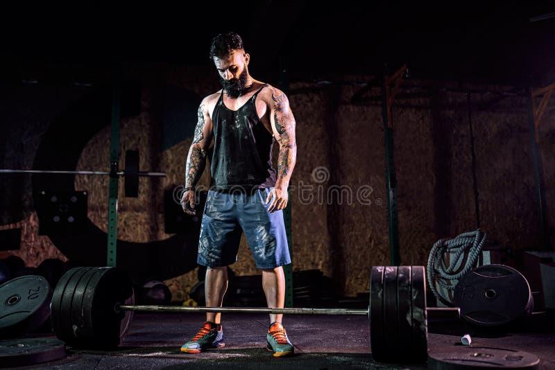 Hombre muscular de la aptitud que se prepara al deadlift de un barbell en centro de aptitud moderno Entrenamiento funcional fotos de archivo