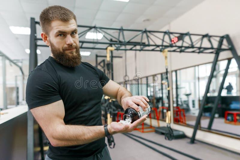 Hombre muscular deportivo que muestra deportes y los suplementos de la aptitud, cápsulas, píldoras, fondo del gimnasio Forma de v imagen de archivo