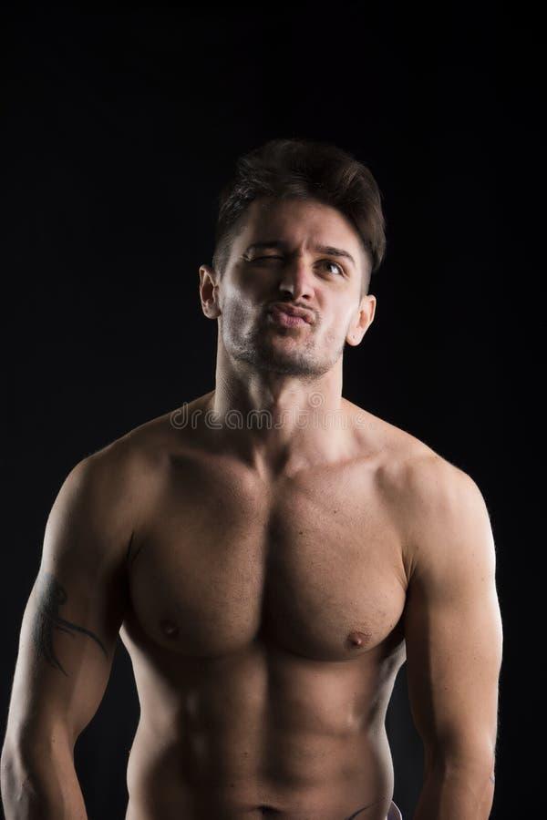Hombre muscular, descamisado hermoso que mira para arriba imagen de archivo