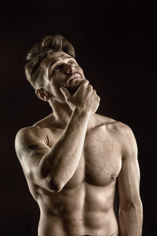 Hombre muscular, descamisado hermoso que mira para arriba de pensamiento imágenes de archivo libres de regalías